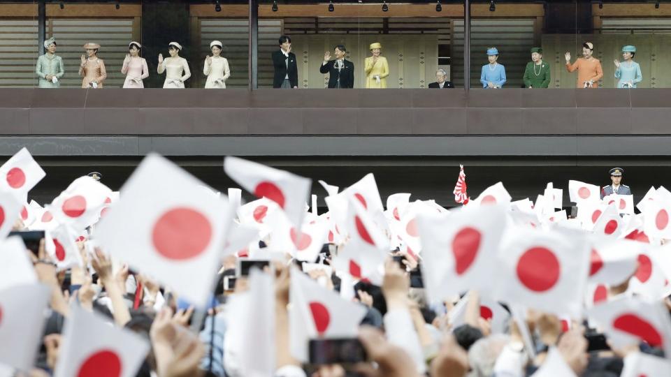خانواده امپراتور ژاپن در کاخ امپراتوری برای مردم دست تکان می دهند