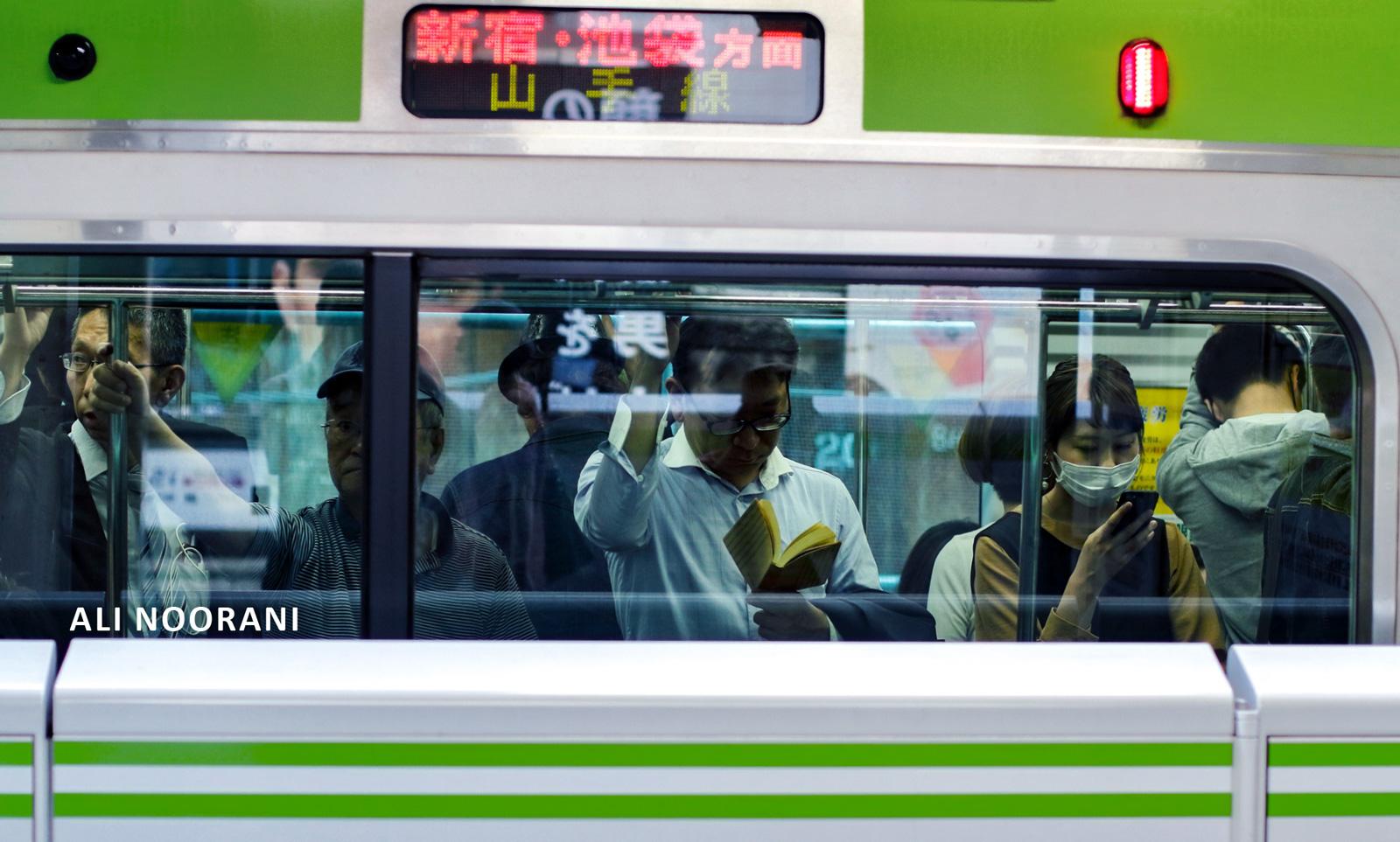 مردی در حال کتاب خواندن در مترو توکیو. عکس از علی نورانی